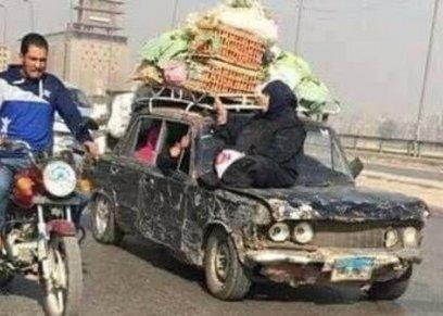 صورة لسيدة تجلس على سيارة متهالكة تحمل بضاعتها