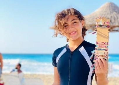 الطفلة  «فاتيما» تبيع الإكسسوارات على الشاطئ