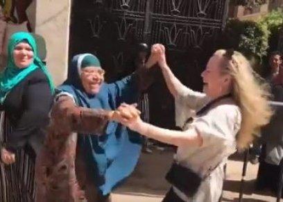 سيدة أمريكية ترقص مع إحدى السيدات المصريات من أمام اللجنة الانتخابية