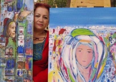 الفنانة التشكيلية السورية عتاب حريب وسط لوحاتها