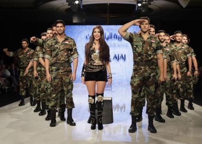 المصممة السورية منال عجاج تقف وسط عارضي أزياء يرتدون زي الجيش