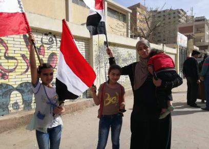 أم وأطفالها بعلم مصر خلال مشاركتها في الانتخابات: