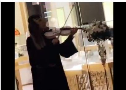 سعودية تعزف الكمان أمام إحدى المتاجر