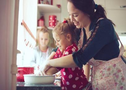 أم وبناتها تعد لهن الطعام