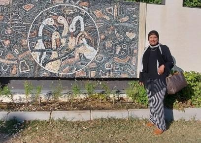 الدكتورة منى علي رجب بجوار أحد أعمالها