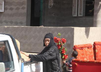 عجوز اثناء تحميلها اثاث منزلها استعدادا لمغادرة قرية الجن فى كفر الشيخ