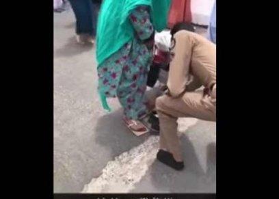 رجل أمن يخلع حذاءه لامرأة مسنة ليقيها من حرارة الأرض