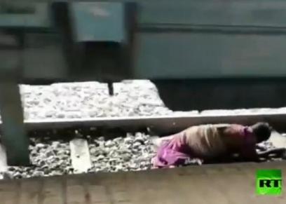 بالفيديو ..عجوز هندية تستلقى بين عجلات القطار أثناء عبور القضبان