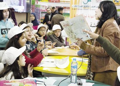 سماح أبوبكر مع الأطفال فى ورشة الحكى بمعرض الكتاب