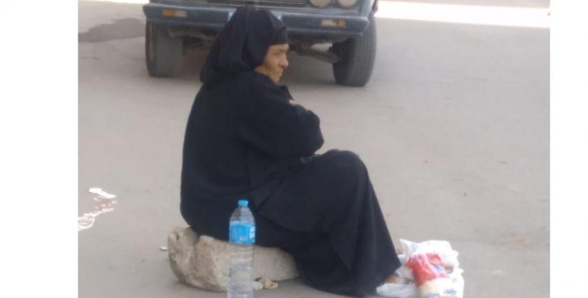 عجوز تفترش الرصيف لبيع حصتها التموينية