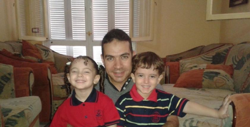 الشهيد أحمد المنيري وهو يتوسط طفليه دارين ومصطفي