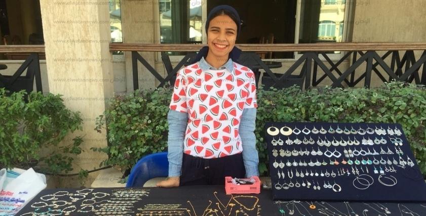 إسراء تقف أمام كلية فنون جميلة لبيع المشغولات اليدوية