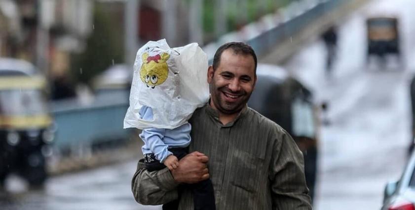 أب يخفي طفلته داخل كيس بلاستيك لحمايتها من الأمطار